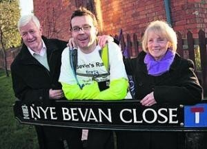 Dr Clive Peedell between two others behind a road sign for Nye Bevan Close