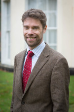 in a red tie and tweed jacket Occupational Health Expert Dr Grant Charlesworth-Jones